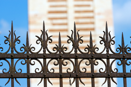 Old and rusty wrought iron fence on blue sky and blurry architecture