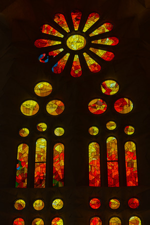 Stained glass window of colored glass in the basilica of the Sagrada Familia in Barcelona, Catalonia, Spain