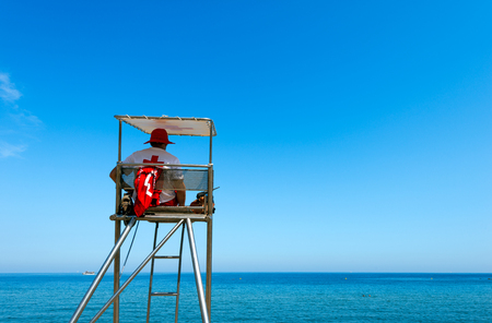Lifeguard sitting on surveillance steel tower watching the sea with portable radio transceiver