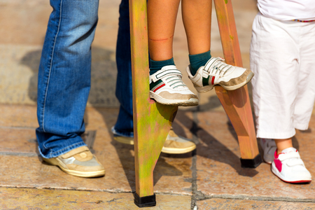 An adult helps a child to walk on wooden stilts, view of sun legs and feet photo