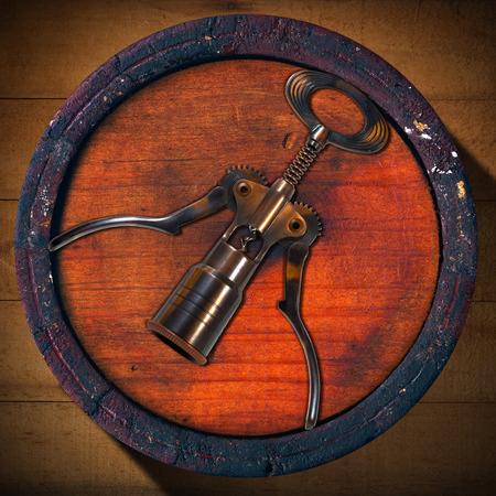 Old wooden barrel with a corkscrew on the background of wooden boards photo