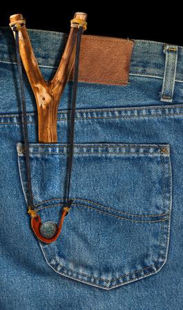 Old handmade slingshot in the back pocket of blue jeans photo