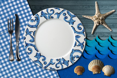 Empty plate with fork and knife, blue and white checkered tablecloth, seashells, blue waves and starfish. Table set for a seafood menu photo