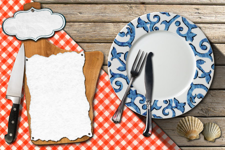 Restaurant fish menu with cutting board, empty label and white paper, empty plate with silver cutlery on wooden background with seashells and checkered tablecloth photo