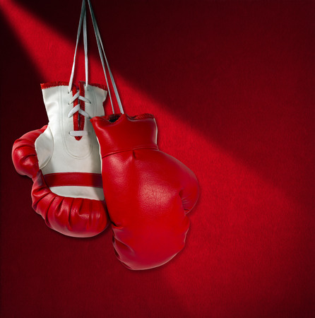 renounce: Pair of red and white boxing gloves hanging on red velvet wall with shadows
