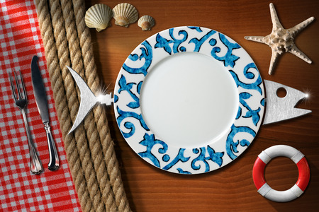 Empty plate with cutlery, seashells, starfish and lifebuoy on wooden table with ropes and red and white tablecloth. Table set for a seafood menu photo