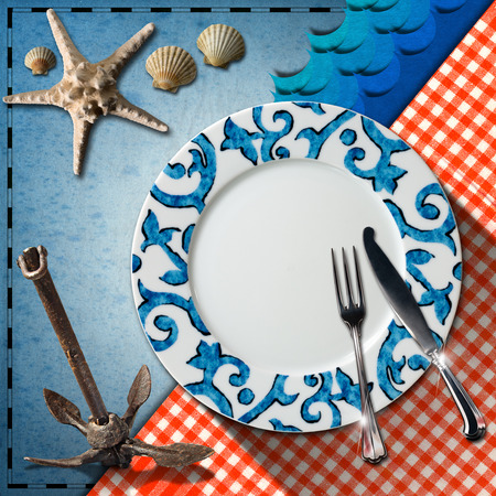 Empty plate with fork and knife, red and white checkered tablecloth, seashells, starfish, blue waves and rusty anchor. Table set for a seafood menu photo