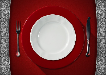 Empty and white plate on red underplate with silver cutlery, fork and knife on red velvet background with silver floral decorations photo