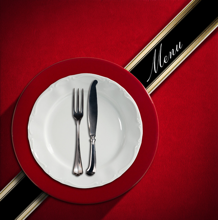 Restaurant menu with empty and white plate on red underplate with silver cutlery, fork and knife on red velvet background with diagonal band photo