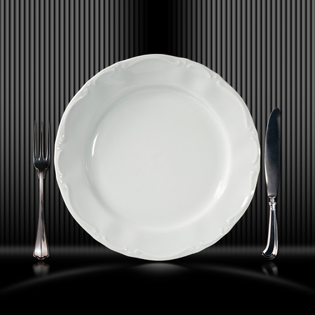 Empty plate on black and white and gray corrugated background with silver cutlery, fork and knife photo
