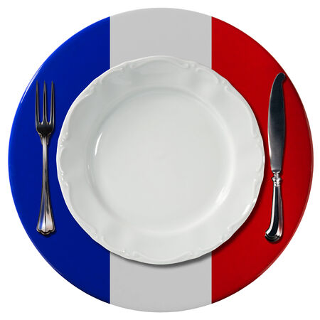 Concept of French cuisine with white plate and under plate colored with the colors of the French flag and silver cutlery isolated on white background photo