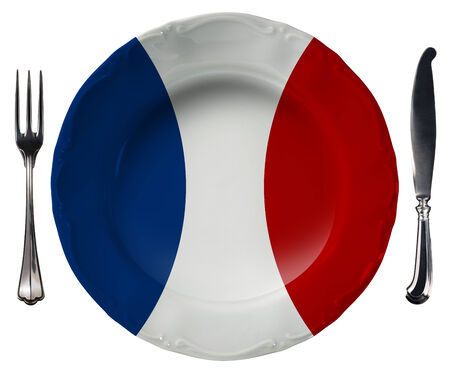 Concept of French cuisine with empty plate colored with the colors of the French flag and silver cutlery isolated on white background photo