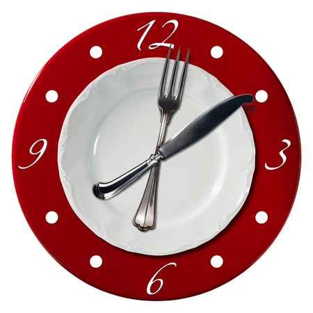 plate setting: Clock composed by a white plate and a red underplate with fork and knife in the place of the clock hands. Lunch time concept