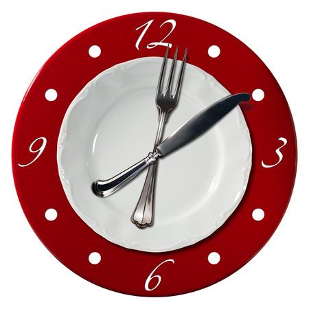 plato de comida: Reloj compuesto por un plato blanco y una placa inferior de color rojo con un tenedor y un cuchillo en el lugar de las manecillas del reloj. Concepto de la hora del almuerzo