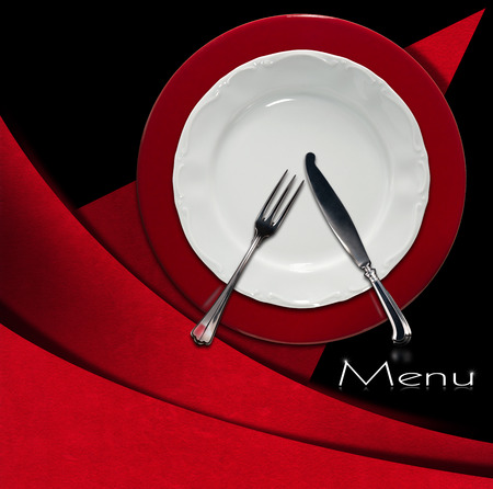 Restaurant menu with empty plate on red and white underplate with silver cutlery, fork and knife on red and black background with geometric shapes photo