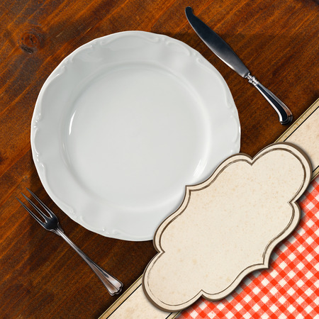 Restaurant menu with empty white plate with silver cutlery, on wooden background with red and white tablecloth and empty label photo