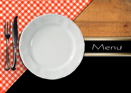 Restaurant menu with empty white plate with silver cutlery, on wooden background with red and white tablecloth and horizontal black band photo