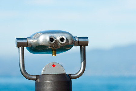 Coin operated electronic binoculars for tourist against blue blurred background photo
