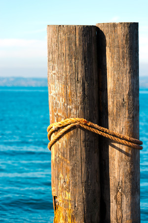 Detail of two wooden bollards with rope at Garda Lake in Italy
