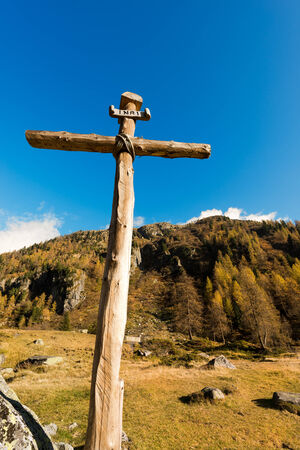 inri: Old wooden cross (trunks of trees) tied with ropes with blue sky and clouds in the National Park of Adamello Brenta. Trentino Alto Adige, Italy Stock Photo
