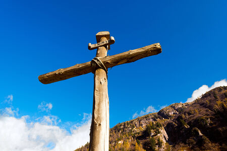 Old wooden cross (trunks of trees) tied with ropes with blue sky and clouds in the National Park of Adamello Brenta. Trentino Alto Adige, Italy photo