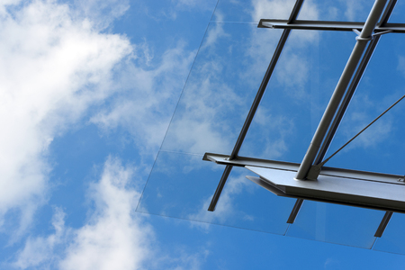 Detail of steel and glass roof of a modern building with blue sky and clouds photo
