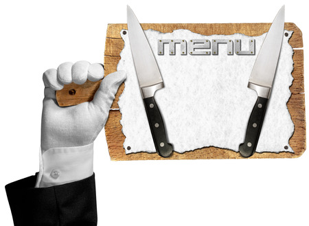 Hand of waiter with white glove holding a old wooden cutting board with empty white sheet of paper, two kitchen knives and written menu photo