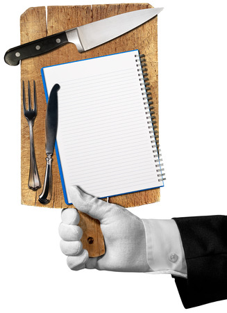 Hand of waiter with white glove holding a old wooden cutting board with notebook, kitchen knife and silver cutlery isolated on white background photo