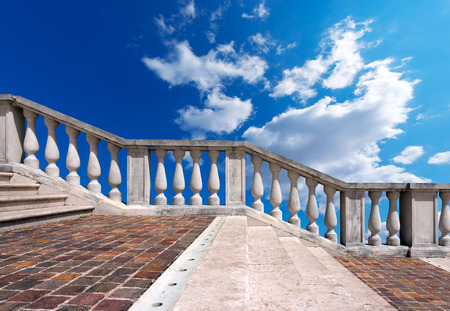 Staircase in white stone and marble with balustrade on blue sky with clouds photo