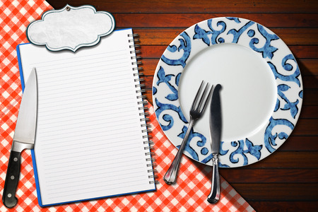 Empty plate with silver cutlery and kitchen knife, open notebook for recipes or menu with label on wooden table with red and white checkered tablecloth photo