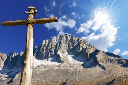 Old wooden cross (trunks of trees) tied with ropes with blue sky, clouds and sunlight in the National Park of Adamello Brenta. Trentino Alto Adige, Italy