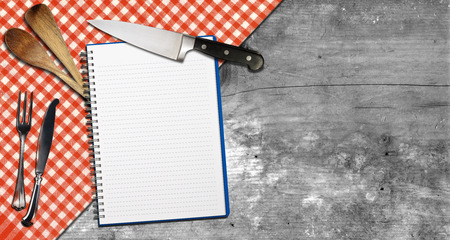 Empty open notebook for recipes or menu with silver cutlery, kitchen knife, two wooden spoons or ladles on grey wooden background with red and white checkered tablecloth photo