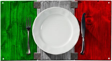 Concept of Italian cuisine with empty white plate and silver cutlery on Italian wooden flag isolated on white background photo