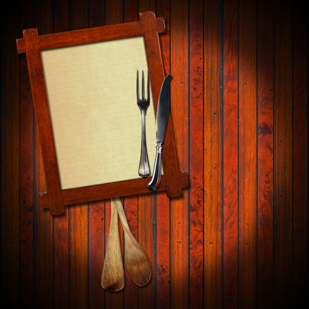 Wooden frame with a blank sheet of paper, two wooden spoons and silver cutlery on wooden background. Template for recipes or food menu photo