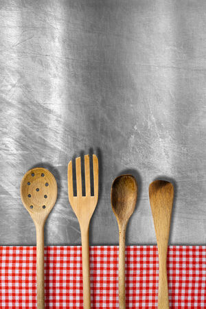 food: Four wooden kitchen utensils, fork, spoons and ladles on metallic background with red and white checkered tablecloth. Stock Photo