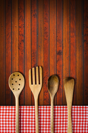 Four wooden kitchen utensils, fork, spoons and ladles on dark wooden background with red and white checkered tablecloth. photo