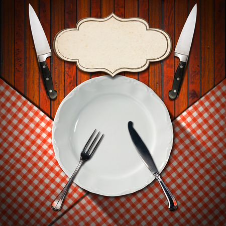 Empty and white plate on wooden brown background and red and white checkered tablecloth with silver cutlery, two kitchen knives and empty label photo