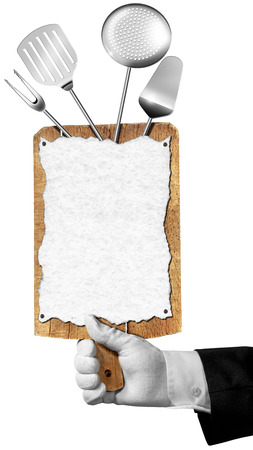 Hand of waiter with white glove holding a old wooden cutting board with empty sheet of paper and kitchen utensils isolated on white background photo