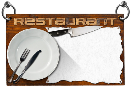 Advertising dark wooden sign with clipping path for a restaurant with a white empty sheet of paper, kitchen knife, empty white plate and silver cutlery photo