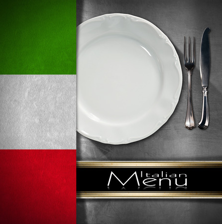 Metallic background with textile italian flag, empty white plate with silver cutlery, fork and knife and black horizontal band. Template for food Italian menu photo