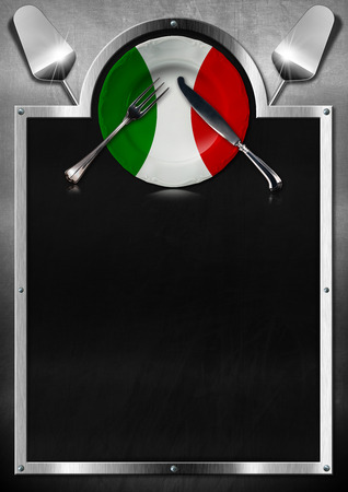 Empty blackboard on metallic background with empty plate colored with the colors of Italian flag, silver cutlery and kitchen utensils. Template for recipes or Italian food menu photo