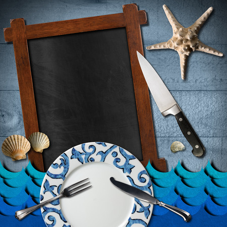 Blackboard with wooden frame, stylized sea waves, empty plate and cutlery, kitchen knife, seashells and starfish on blue wooden background. Template for recipes or seafood menu photo