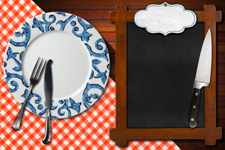Empty plate with silver cutlery and kitchen knife, empty blackboard for recipes or menu with label on wooden table with red and white checkered tablecloth photo