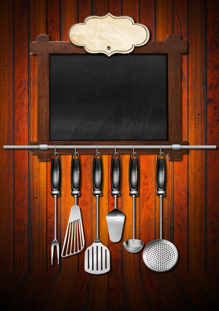 Empty blackboard with wooden frame, empty label, a set of kitchen utensils hanging on a steel pole, on a wooden wall. Template for a recipes or a food menu photo