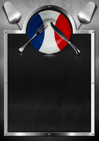 Empty blackboard on a metallic background with empty plate colored with the colors of French flag, silver cutlery and kitchen utensils. Template for recipes or French food menu photo
