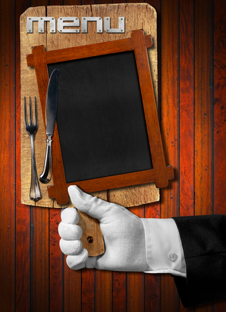 Hand of waiter with white glove holding a old wooden cutting board with empty blackboard and silver cutlery on wooden dark background. Template for recipes or food menu photo