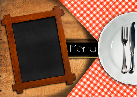 Food menu with white plate, silver cutlery and empty blackboard on wooden background with tablecloth and horizontal black band photo