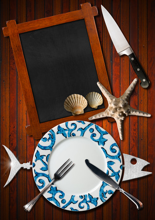 silver cutlery: Restaurant seafood menu with metal fish, empty blackboard, empty plate with silver cutlery, starfish, seashells and kitchen knife on wooden background Stock Photo