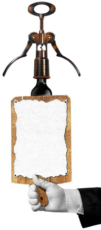 Hand of sommelier with white glove holding a old wooden cutting board with empty sheet of paper and old corkscrew with black wine bottle. Template for wine list or menu photo
