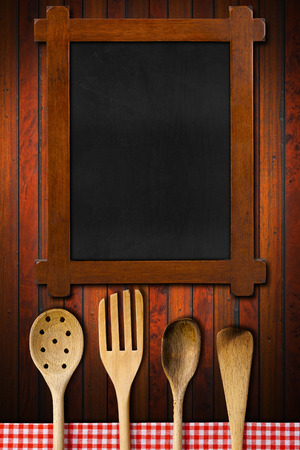 Rustic and empty blackboard, four wooden kitchen utensils, fork, spoons and ladles on dark wooden background with red and white checkered tablecloth photo